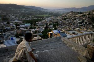 In this May 15, 2011 file photo, Ali Raza sits on the rooftop of his house as he views the city of Abbottabad, Pakistan.