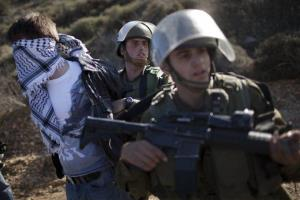 Israeli soldiers detain an activist during clashes that erupted after the funeral of Palestinian Mustafa Tamimi in the West Bank town of Nabi Saleh, Sunday, Dec. 11, 2011.