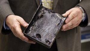 National Transportation Safety Board's Joseph Kolly holds an fire-damaged battery from a Boeing flight in Washington, Thursday, Jan. 24, 2013.