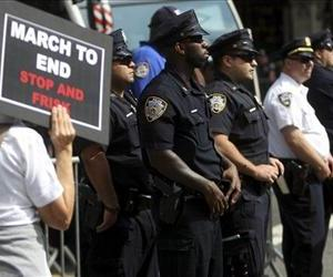 Police officers moniter a silent march to end the stop-and-frisk program in New York, Sunday, June 17, 2012.