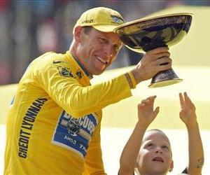 Luke Armstrong tries to touch the winner's trophy held by his father, Lance Armstrong, after Armstrong won his seventh straight Tour de France cycling race, in Paris, in this 2005 file photo.
