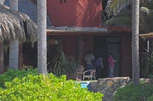 Police investigators work at the Acapulco beach house where the attack took place.