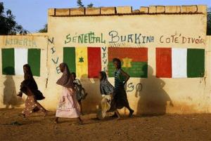 Malian girls walk past a wall decorated with flags of African countries participating in operation Serval in Gao, northern Mali.