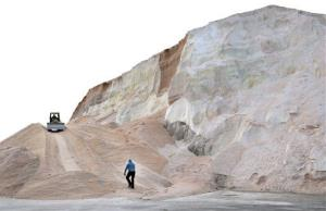 A worker walks up toward a plow smoothing a large salt pile at Eastern Salt Company in Chelsea, Mass., in preparation for a major winter storm.