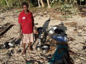 In this Wednesday Feb. 6, 2013 photo provided by World Vision, a woman stands next to her belongings she found along a beach at Venga village after tsunami hit Temotu province, Solomon Islands.