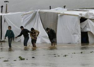 Syrian refugee boys make their way in flooded water at a temporary refugee camp in eastern Lebanon.