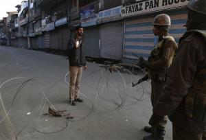 Indian paramilitary soldiers interrogate a civilian near a barbed wire set up as road blockade during curfew in Srinagar, India, Saturday.
