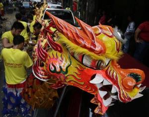 Dragon dancers take a break after performing in front of Chinese business establishments on the eve of Chinese New Year celebration in Manila.