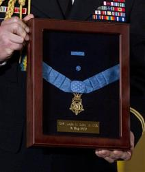 A military aid holds the Medal of Honor during a ceremony in the East Room of the White House in Washington, Wednesday, May 16, 2012.