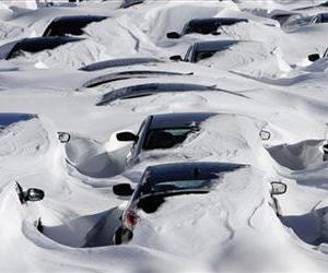 Snow begins to melt on cars parked at a dealership after a winter storm in Hartford, Conn., Sunday, Feb. 10, 2013.