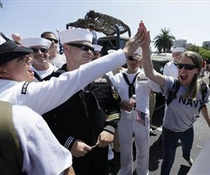 Navy sailors high-five before the gay pride parade Saturday, July 21, 2012, in San Diego.