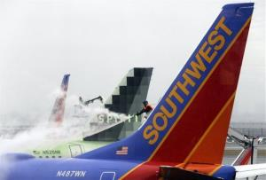 Grounds crews prepare a plane for flight at LaGuardia Airport Friday, Feb. 8, 2013, in New York.