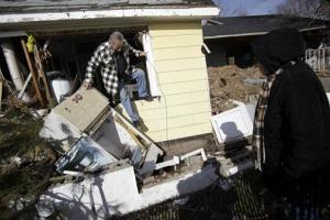 In this Nov. 20 file photo, Joe Vanvaketis climbs out of his home, which was severely damaged by Superstorm Sandy, in the Oakwood Beach section of Staten Island.