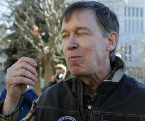Colorado Gov. John Hickenlooper savors a bite of the lamb chops he grilled to show Maryland Gov. Martin O'Malley how they are prepared, Thursday, Jan. 17, 2013 at the Capitol in Denver.