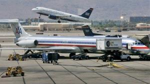 In this file photo, a US Airways jet takes off as an American Airlines jet is prepped for takeoff at Sky Harbor International Airport in Phoenix.