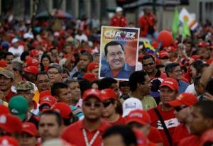 A supporter of Venezuela's President Hugo Chavez holds up a poster while marching in a parade marking the anniversary of a 1992 failed coup attempt led by Chavez, in Caracas, Monday, Feb. 4, 2013.