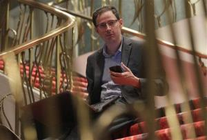 Nate Silver holds his phone as he sits on the stairs with his laptop computer at a hotel in Chicago last year.