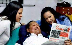 Hugo Chavez poses with his daughters as he holds a copy of Cuba's state newspaper Granma, somewhere in Havana, Cuba, in this photo released today by the Miraflores Presidential Press Office.