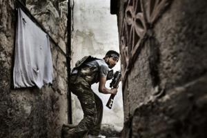 A Free Syrian Army (FSA) fighter takes position during the clashes against Syrian government forces in Sulemain Halabi district in Aleppo, Syria, Oct. 10, 2012.