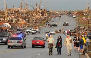 In this May 22, 2011 file photo, residents of Joplin, Mo., walk west on 26th Street near Maiden Lane after a tornado hit the southwest Missouri city.