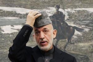 Afghan President Hamid Karzai adjusts his hat as he speaks during a press conference at the presidential palace in Kabul, Afghanistan, Monday, Jan. 14, 2013.