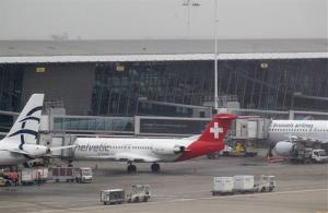 Baggage carts make their way past a Helvetic Airways aircraft from which millions' of dollars worth of diamonds were stolen on the tarmac of Brussels international airport, Tuesday, Feb. 19, 2013.