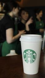 A coffee cup bearing the new Starbucks Corp. logo is shown.