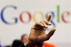 In this Oct. 17, 2012, file photo, a man raises his hand at Google offices.