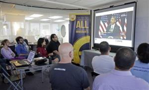 Illegal immigrants and immigration activists watch President Obama speaking about immigration reform, Jan. 29, 2013.