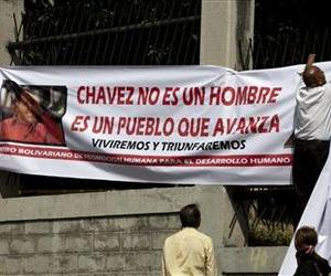 A man hangs a pro-Chavez banner outside the hospital where Hugo Chavez is receiving treatment in Caracas.