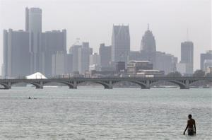 A swimmer walks in the Detroit River at Belle Isle in Detroit, with the city skyline behind him in this file photo.