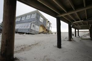 A raised home with modest damage is seen near a severely damaged beach front home in Mantoloking, N.J., Friday.