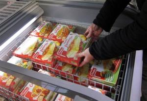 In this Feb. 11, 2013 file photo, a customer takes a pack of frozen beef Hachis Parmentier from a freezer in a supermarket in Nice, southeastern France.