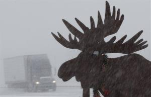 A truck drives in near whiteout conditions past a silhouette of a moose on Interstate 80 near Gretna, Neb.