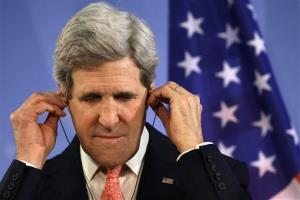 Secretary of State John Kerry adjusts his translation earphones while listening to German Foreign Minister Guido Westerwelle at a news conference in Berlin.