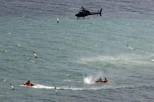 Police in inflatable rubber boats shoot at a shark off Muriwai Beach near Auckland, New Zealand today.