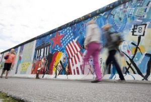 Tourists walk along the East Side Gallery, a painted section of the Berlin Wall in Berlin, Germany, Friday, Aug. 10, 2012.