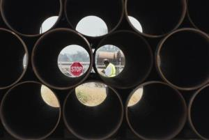 In this 2012 file photo, a man walks past some of about 500 miles worth of coated steel pipe in a Little Rock, Ark., storage yard that was originally produced for the Keystone oil pipeline.