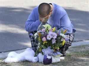 Jeremy Bush places flowers and a stuffed animal at a makeshift memorial in front of a home where his brother Jeffrey died in a sinkhole in Seffner, Fla. on Saturday, March 2, 2013.