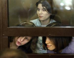 Pussy Riot members Maria Alekhina, left, Yekaterina Samutsevich,  top, Nadezhda Tolokonnikova,are seen behind a glass wall at a court in Moscow, Russia, Monday, July 30, 2012.