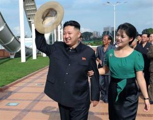 In this July 25, 2012 file photo, Kim Jong Un, accompanied by his wife Ri Sol Ju, waves to the crowd as they inspect the Rungna People's Pleasure Ground in Pyongyang, North Korea.