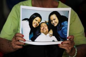 In this Feb. 15, 2013, file photo, a woman holds a copy of a photo released by the government, showing Hugo Chavez at a Havana hospital with two of his daughters, in Caracas, Venezuela.