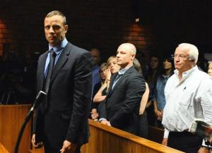 Olympian Oscar Pistorius, foreground, stands following his bail hearing, as his brother Carl, centre, and father Henke, right, look on,  in Pretoria, South Africa, Tuesday, Feb. 19, 2013.
