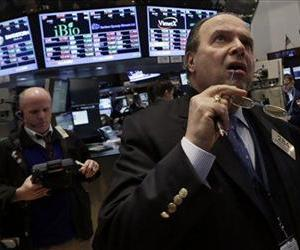 Trader Donato Cuttone, right, works on the floor of the New York Stock Exchange, Feb. 28, 2013.