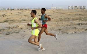 Palestinian runners, Nader Al Masri, left, and Mahmoud Yousef, participate in the first Gaza marathon in 2011.