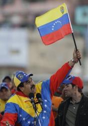 Venezuela's Vice President Nicolas Maduro holds up a Venezuelan flag.