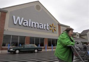 In this Tuesday, Nov. 13, 2012 photo a woman pushes a shopping cart away from the entrance of a Walmart store in North Kingstown, RI.