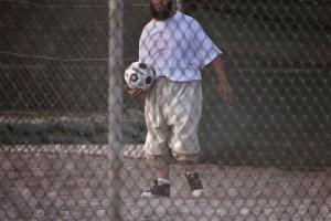 In this photo taken May 13, 2009, a Guantanamo detainee holds a soccer ball, just before dusk, inside the exercise yard at Camp 4 detention facility, at Guantanamo Bay US Naval Base, Cuba.