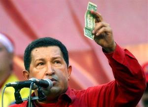 In this Jan. 23, 2005 photo, Venezuela's President Hugo Chavez holds up a US dollar bill and challenges US President George W. Bush to bet which of them will remain in power longer at a rally in Caracas, Venezuela.