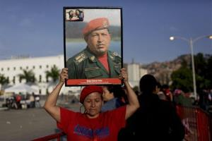A woman holds a photo of Hugo Chavez as she waits in line to see his body lying in state at the military academy in Caracas.
